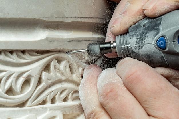 De persoon overhandigt snijdend ornament op pleister