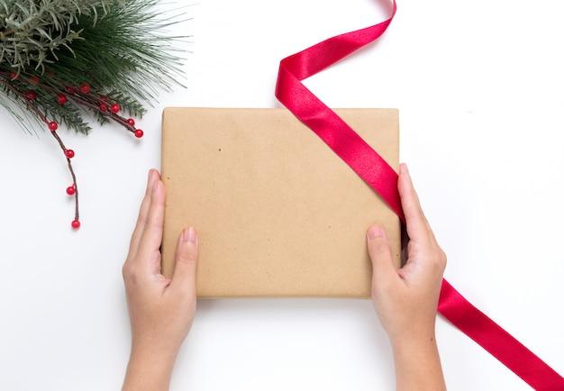 De persoon verpakt kerstmis huidig in ambachtdocument met rood lint