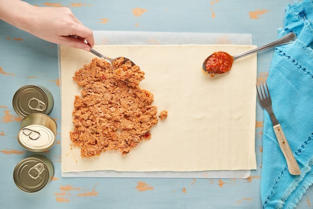 De persoon vult een deeg met tonijn en tomaat om een galicische empanada te bereiden