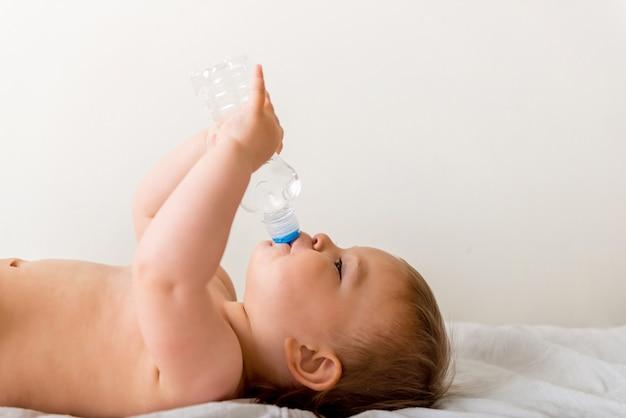 De peuter van de baby zit op het witte bed, glimlacht en drinkt water van plastic fles