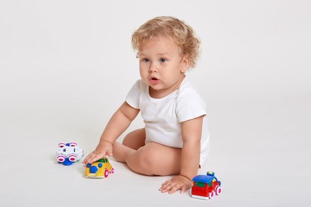 De peuters die van kinderdagverblijfbaby's met kleurenspeelgoed spelen dat op witte ruimte wordt geïsoleerd