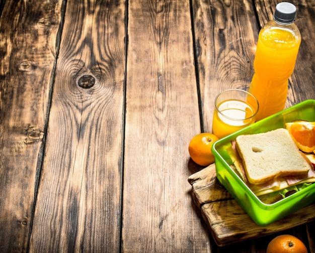 De picknickset sandwiches met kaas en spek, fruit en jus d'orange