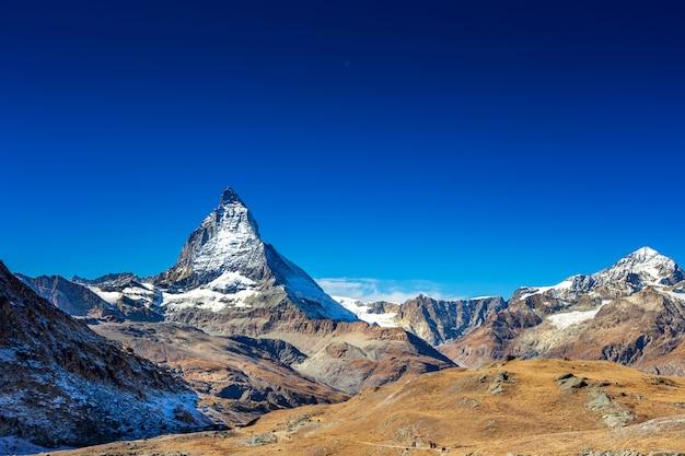 De piekberg van matterhorn in de zomer met duidelijke blauwe hemel en dagmaan in zermatt zwitserland, europa