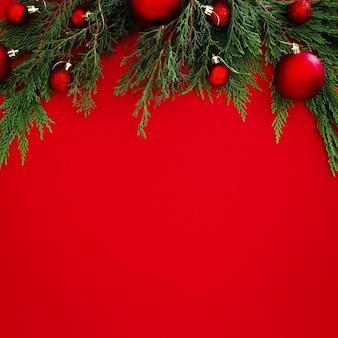 De pijnboombladeren van kerstmis die met rode ballen op rode achtergrond met copyspace worden verfraaid