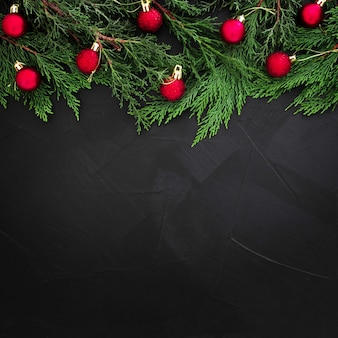 De pijnboombladeren van kerstmis die met rode ballen op zwarte achtergrond met copyspace worden verfraaid