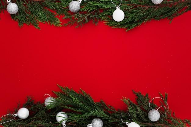 De pijnboombladeren van kerstmis op een rode achtergrond met een lege nota