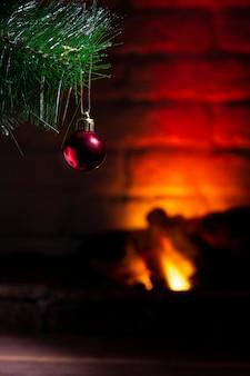 De pijnboomtak van kerstmis met rood balclose-up op een achtergrond van een brandende open haard