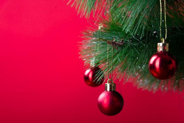De pijnboomtak van kerstmis met rood ballenclose-up op een rode achtergrond