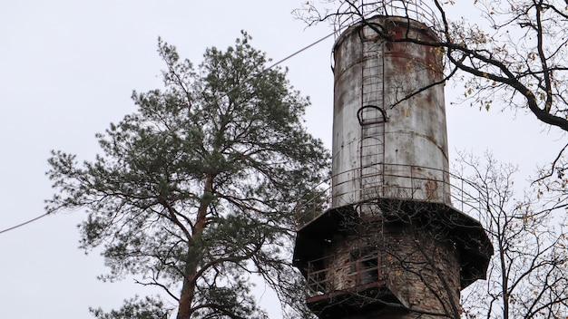 De pijp van de plant steekt boven het bos uit. industrieel landschap. ecologische productie zonder rook uit leidingen. watertoren in het dorp. watervoorziening van huizen onder druk. landelijk landschap.