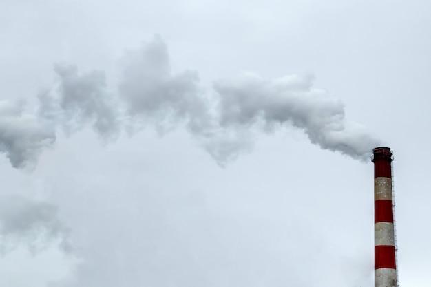 De pijp waarvan de rook tegen de grijze lucht ingaat