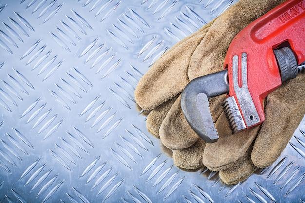 De pijpmoersleutel van leer beschermende handschoenen op gekanaliseerd metaal achtergrondbouwconcept