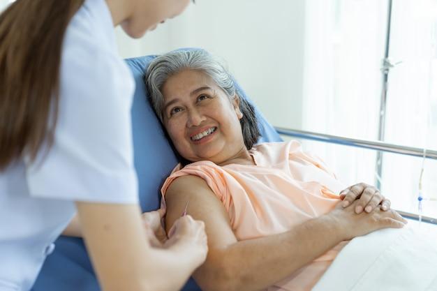 De pil van de de verpleegstersholding van de hand voor het injecteren aan bejaarde vrouwelijke patiënten die op bed met het glimlachen, exemplaar ruimte, gezond en medisch concept liggen