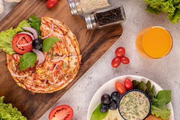 De pizza staat in een houten bakje met daarop rode uien, zwarte druiven, tomaten en sla.