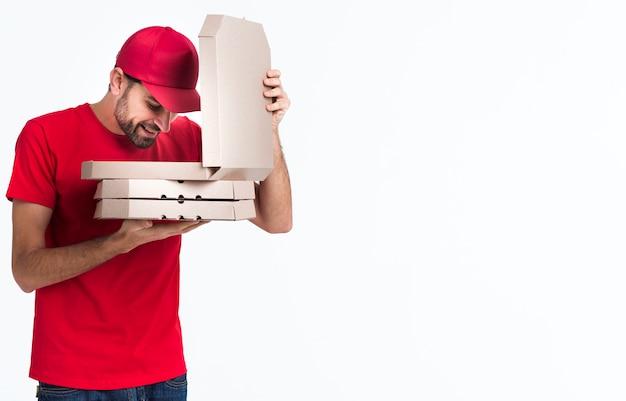 De pizzajongen die van de levering binnen de dozen kijkt