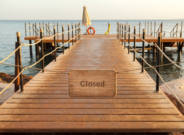 De plaat met het opschrift gesloten op een houten pier
