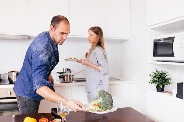 De plaat van de jonge mensenholding van salade in de keuken