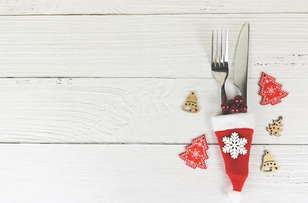 De plaats van de kerstmislijst het plaatsen decoratie met vorkmes in het nieuwjaarvoedsel van de hoedenkerstmis van de kerstman