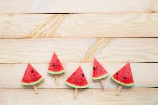 De plakijslollys van de watermeloen op witte houten achtergrond