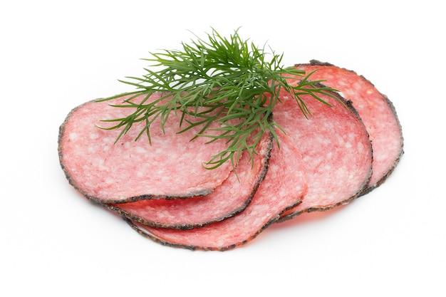 De plakjes van de salamiworst die op wit lijstknipsel worden geïsoleerd