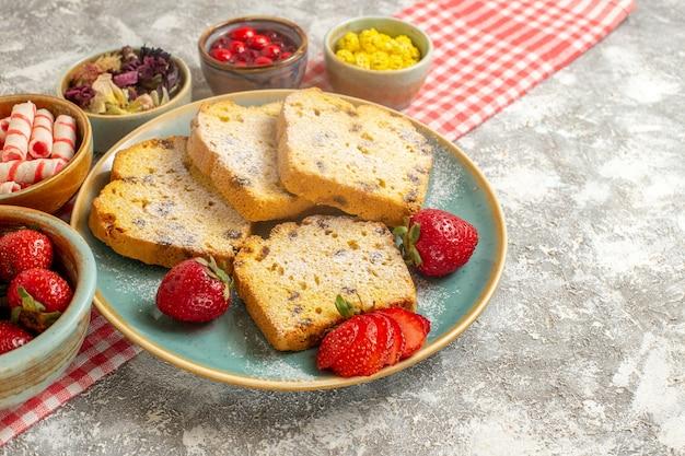 De plakjes van de vooraanzichtcake met verse aardbeien en suikergoed op lichte zoete vruchten van de oppervlaktetaart