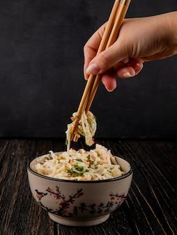 De plakken van de mensenholding met de stijlspaghetti van japan van de kom maakt kruiden zijaanzicht groen