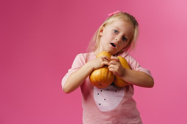 De pompoen van de meisjeholding in haar handen tegen roze achtergrond