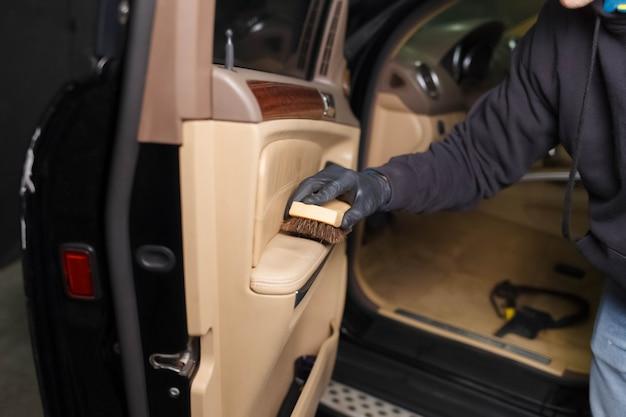 De portierbekleding van de auto schoonmaken met een borstel. detaling concept