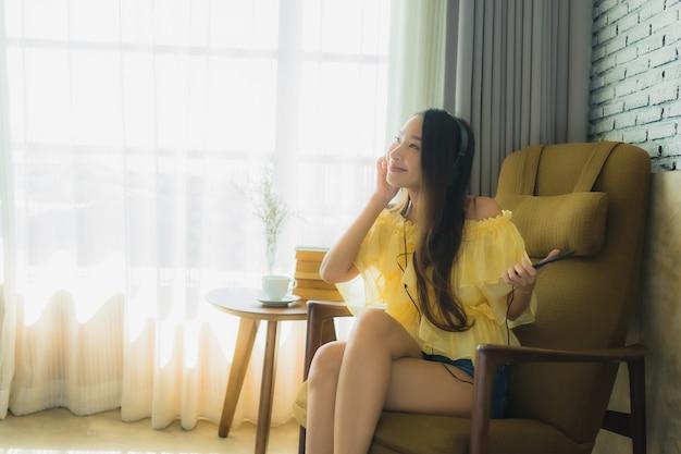 De portret jonge aziatische vrouw zit op stoel luistert muziek met mobiele telefoonkoffie en boek