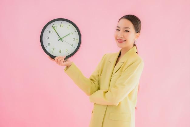 De portret mooie jonge aziatische bedrijfsvrouw toont klok of alarm op geïsoleerde kleur