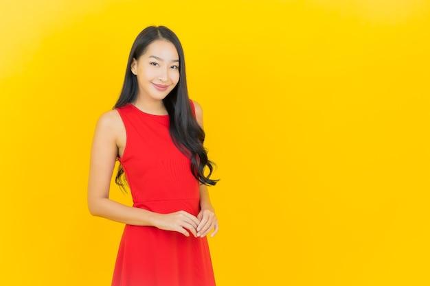 De portret mooie jonge aziatische vrouw draagt rode kledingsglimlach met actie op gele muur