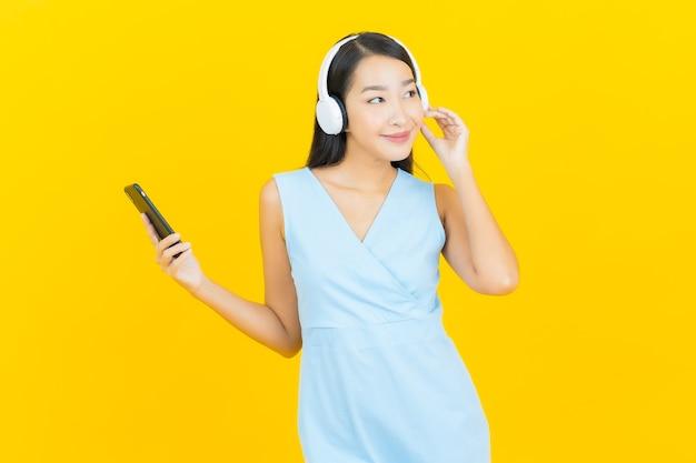 De portret mooie jonge aziatische vrouw met hoofdtelefoon en slimme telefoon voor luistert muziek op gele muur