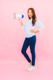 De portret mooie jonge aziatische vrouw met megafoon voor communiceert op roze geïsoleerde muur