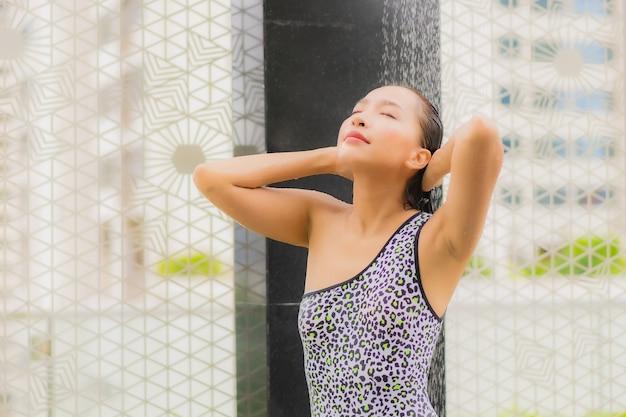 De portret mooie jonge aziatische vrouw neemt een douche rond het buitenzwembad