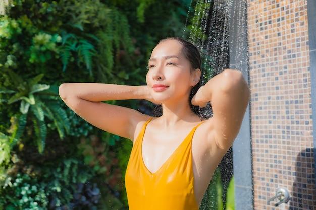 De portret mooie jonge aziatische vrouw ontspant gelukkige glimlach rond openluchtzwembad in hoteltoevlucht voor vrijetijdsvakantie