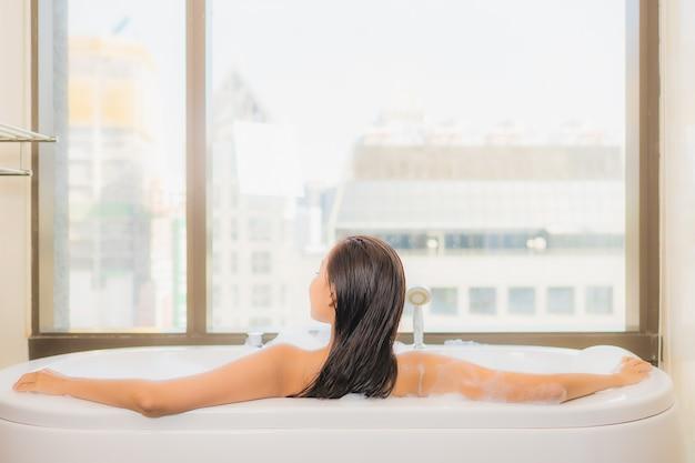 De portret mooie jonge aziatische vrouw ontspant geniet van neemt een bad bij bad in badkamersbinnenland