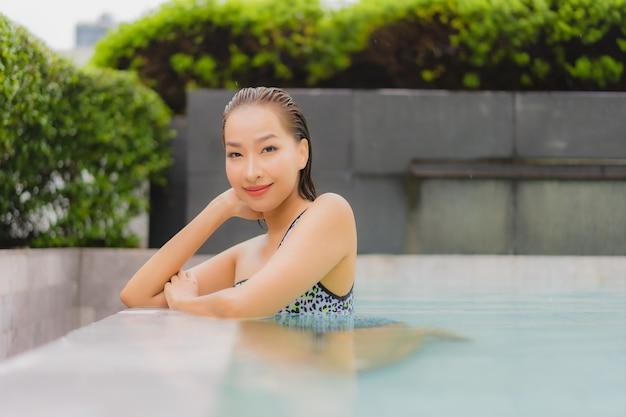 De portret mooie jonge aziatische vrouw ontspant glimlach rond openluchtzwembad voor vrije tijd en vakantie