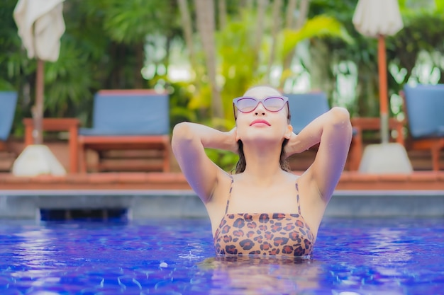 De portret mooie jonge aziatische vrouw ontspant glimlachvrije tijd rond openluchtzwembad in vakantiereizen