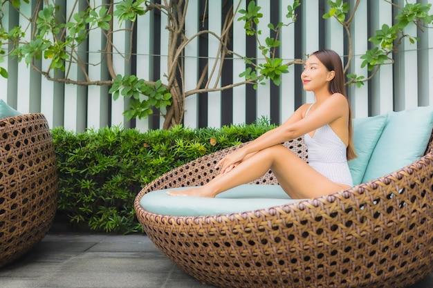 De portret mooie jonge aziatische vrouw ontspant vrije tijd rond openluchtzwembad in hoteltoevlucht voor reisvakantie