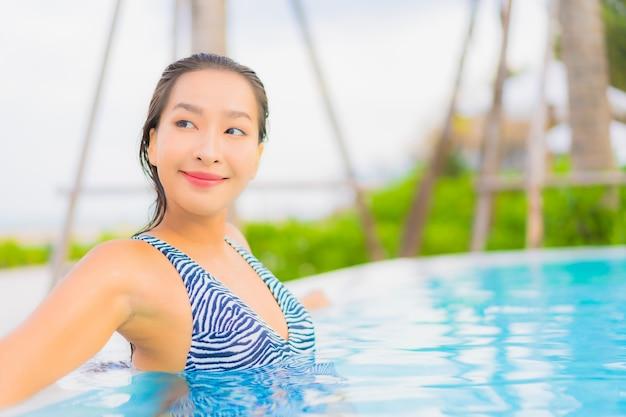 De portret mooie jonge aziatische vrouw ontspant vrije tijd rond openluchtzwembad met overzees oceaanstrand
