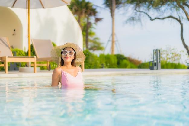 De portret mooie jonge aziatische vrouw ontspant vrije tijd rond openluchtzwembad met overzees