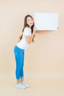 De portret mooie jonge aziatische vrouw toont het lege witte document van de aanplakbordkaart op beige