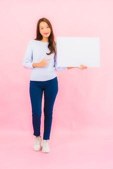 De portret mooie jonge aziatische vrouw toont leeg wit aanplakbord voor tekst op roze kleurenmuur