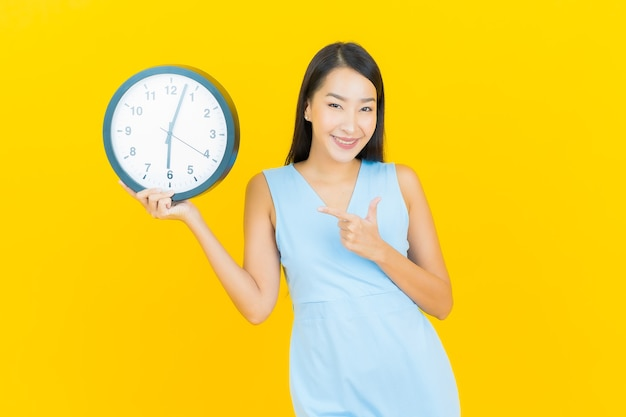 De portret mooie jonge aziatische vrouw toont wekker of klok op gele kleurenmuur