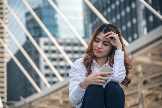 De portretten van mooie aziatische vrouw houden smartphone droefheid van depressie in stedelijk.
