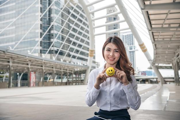 De portretten van mooie aziatische vrouw kijken vertrouwen houdt glimlachbal terwijl zittend.