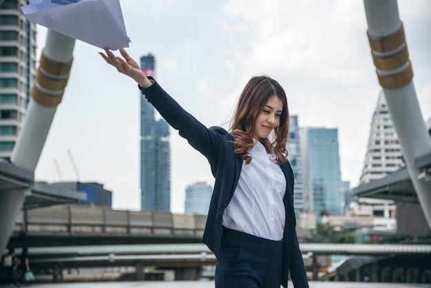 De portretten van mooie aziatische vrouw kijken vrolijk en het vertrouwen bevindt zich en houdt het papierwerk