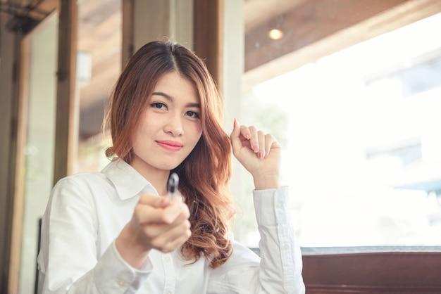 De portretten van mooie aziatische vrouw kijken vrolijk en het vertrouwen houdt pen
