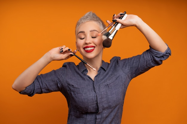De portretvrouw met kort haar met maakt omhoog in hand studioschot