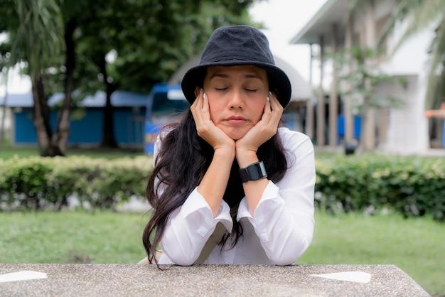 De portretvrouw sluit haar ogen en draagt zwarte hoed