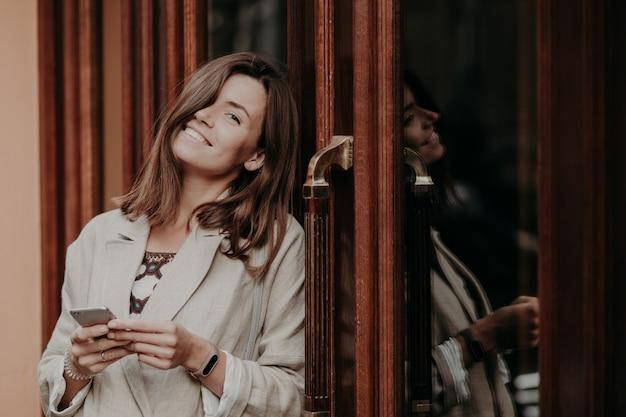 De positieve donkerbruine jonge vrouw met toothy glimlach, draagt smartwatch, gekleed in elegant jasje